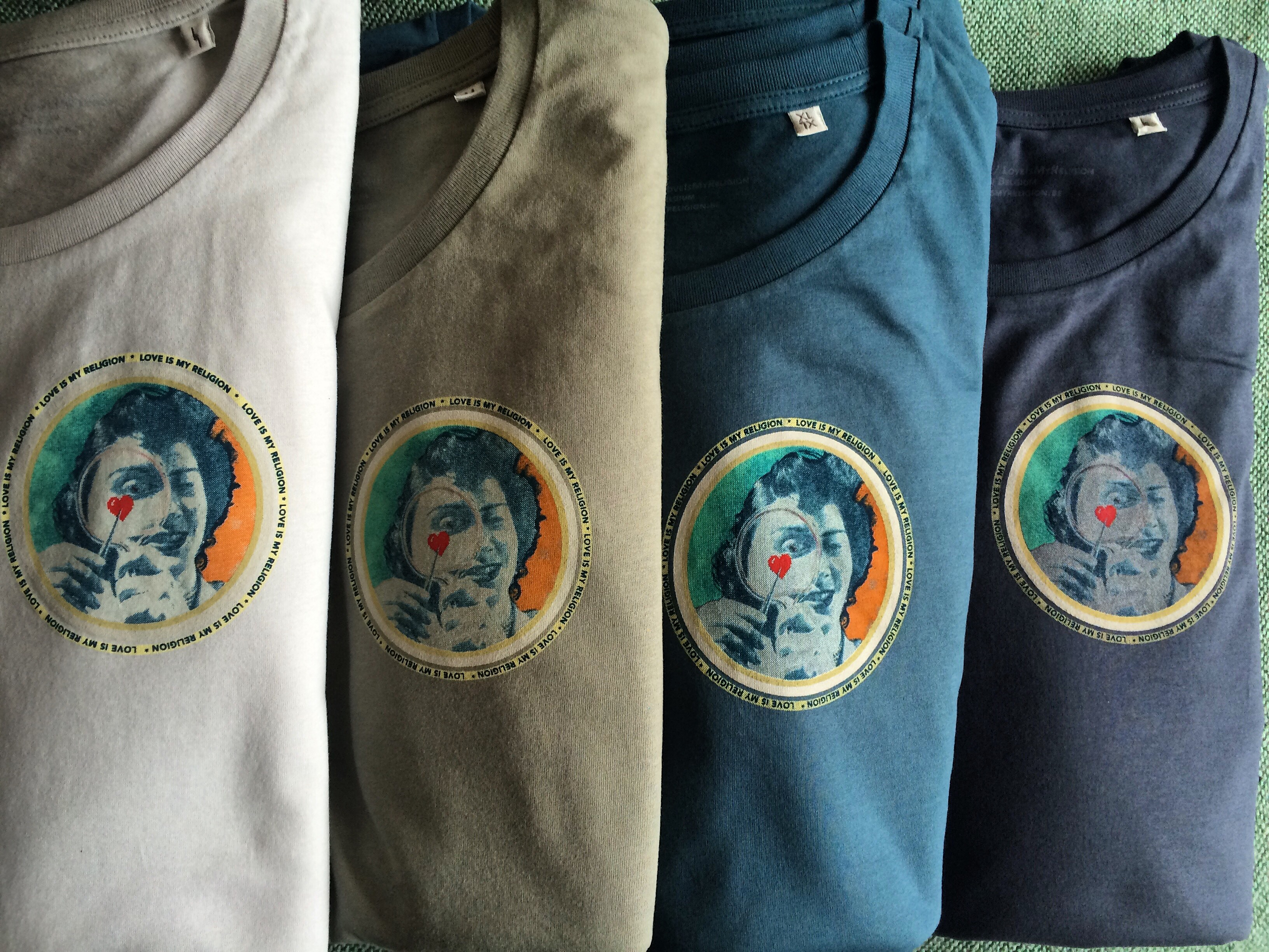 Men's T-shirts in grey-violet, light khaki, petroleum blue, and navy. Design by Sammy Slabbinck on the heart.
